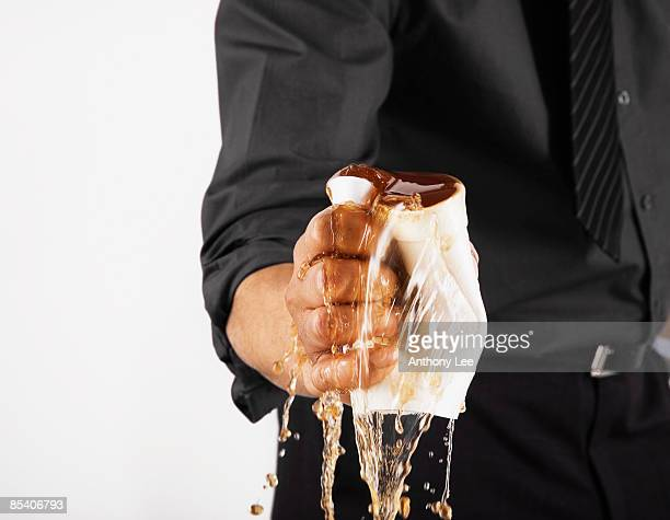 Businessman crushing cup of coffee