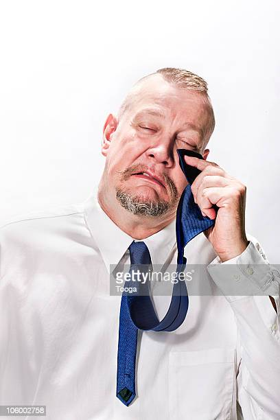 Businessman crying and using tie to wipe his tears