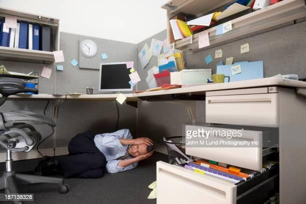 Businessman crying under cubicle desk