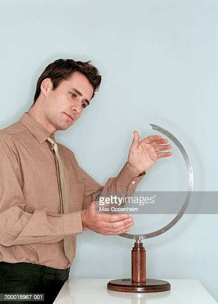 Businessman cupping hands around empty globe stand