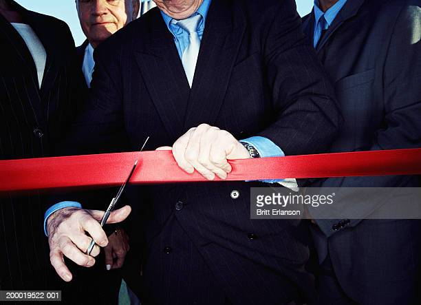 Businessman cutting red tape, close-up