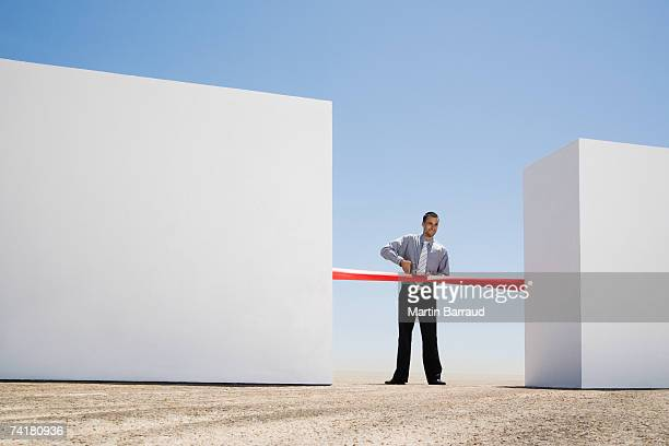 businessman cutting red tape or ribbon between two walls - opening event stock pictures, royalty-free photos & images