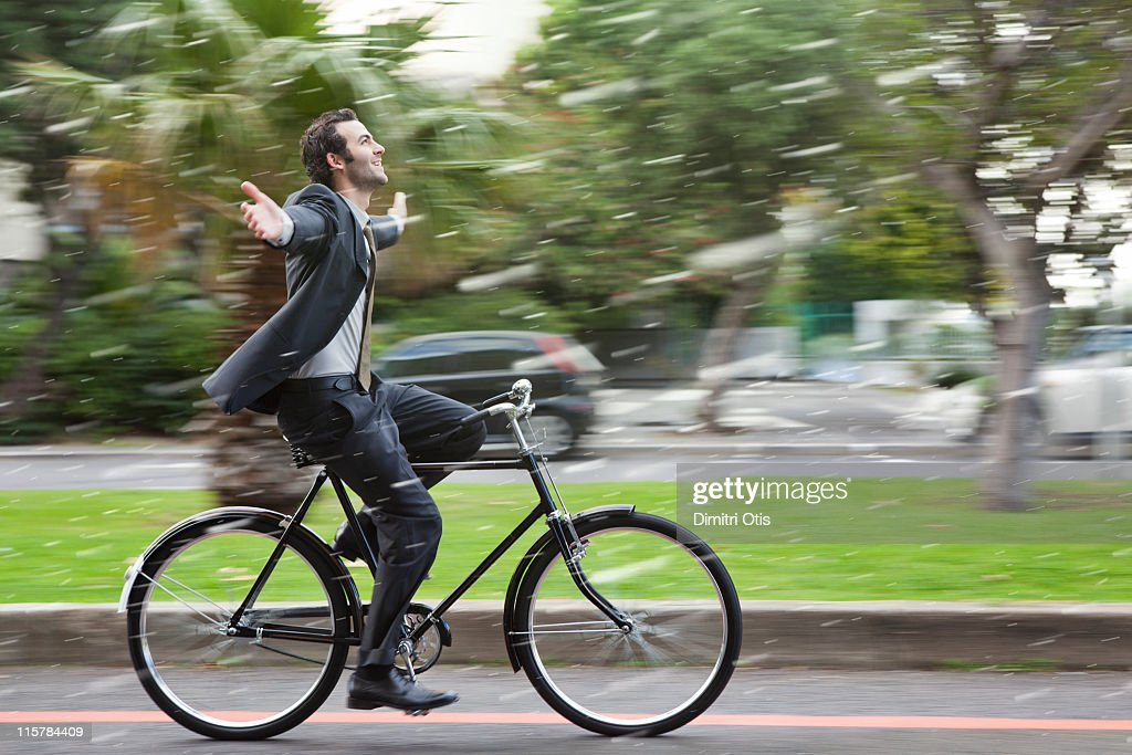 Businessman cycling in the rain, hands in the air : Stock Photo