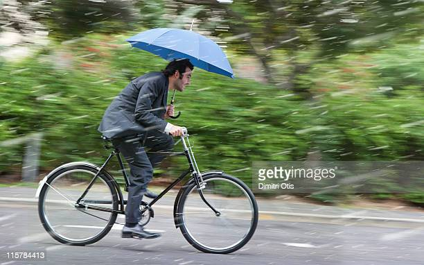 Businessman cycling in the rain with umbrella