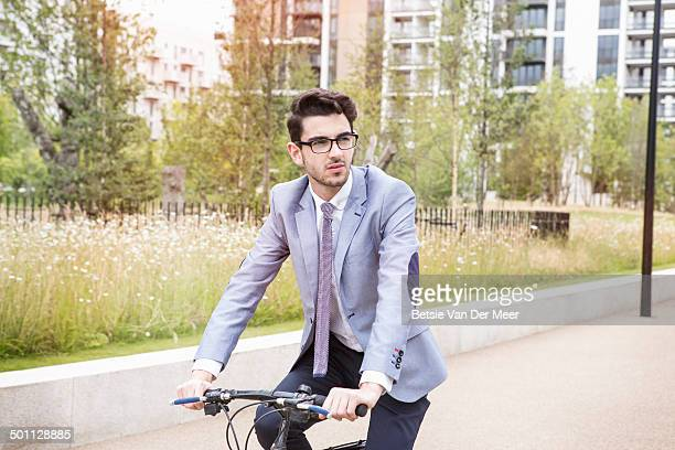 businessman cycling to work in urban park.