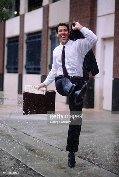 Businessman dancing in the rain