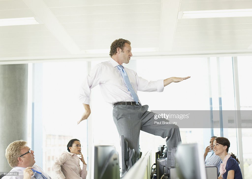 Businessman dancing on cubicle desk : Stock Photo
