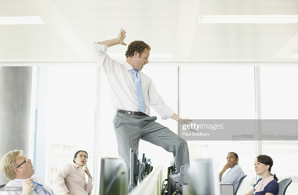 Businessman dancing on desk in cubicle : Stock Photo