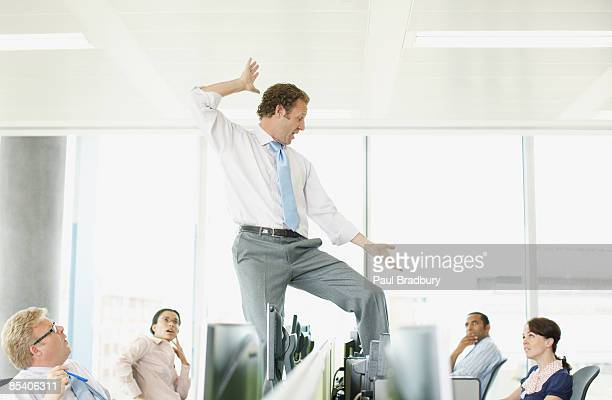 Businessman dancing on desk in cubicle