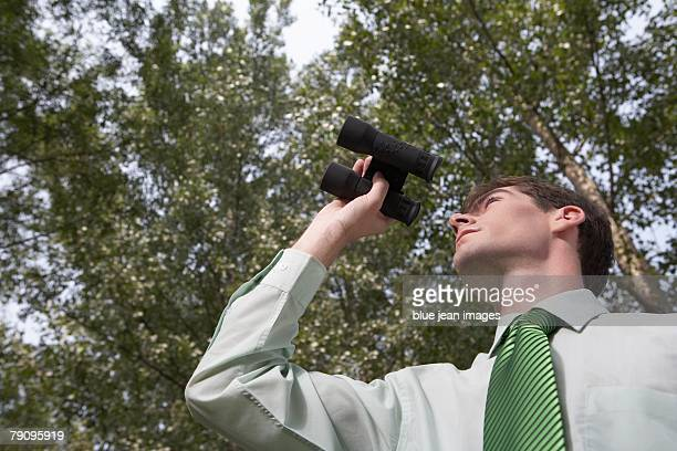 Businessman dazing into the distance with binoculars under the trees.