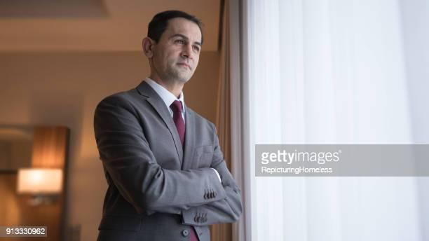 Ein Geschäftsmann guckt Gedanken versunken aus dem Fenster in einem Hotelzimmer