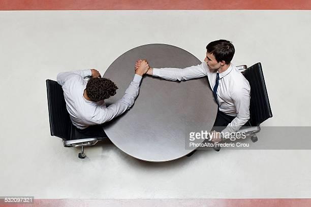 Businessman defeats colleague at arm wrestling match