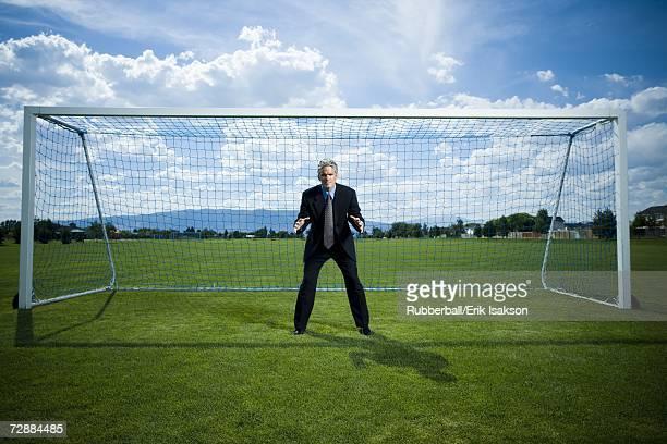 Businessman defending goal on soccer field