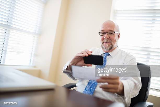 Businessman depositing check via smartphone from his office