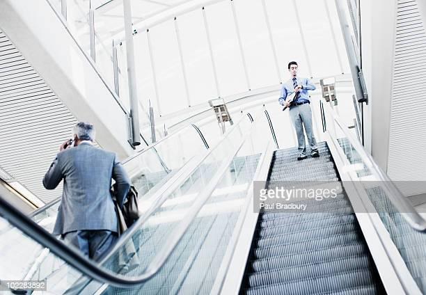 Businessman descending escalator