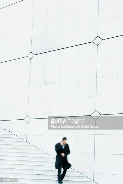 Businessman descending outdoor stairs, talking on cell phone, holding coat closed against the wind