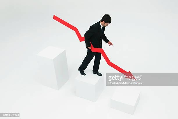 Businessman descending steps holding arrow pointed downward