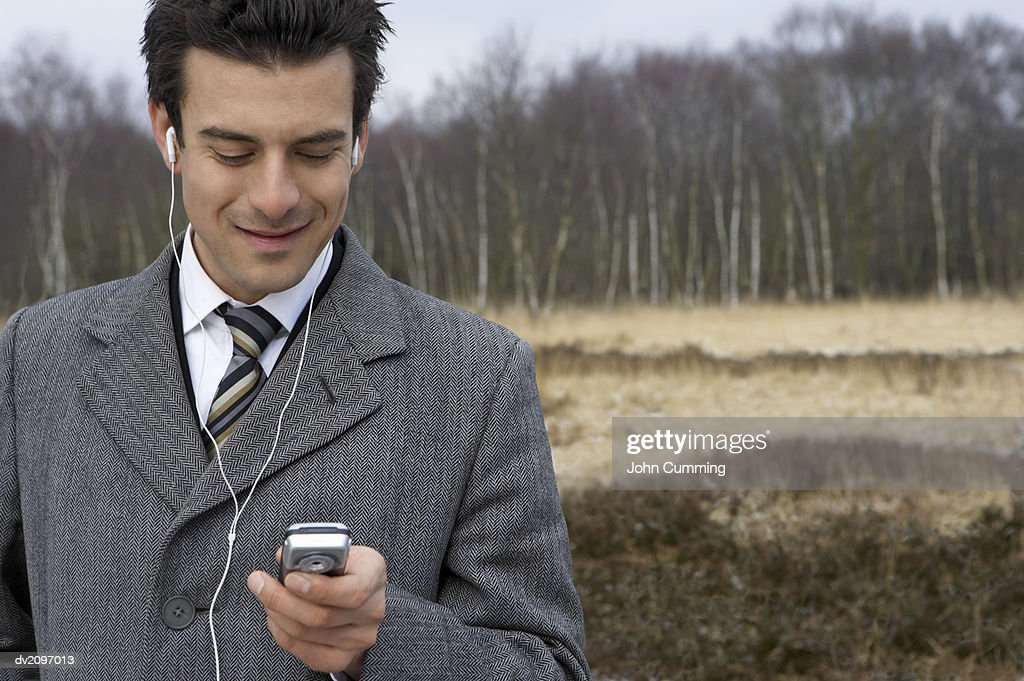 Businessman Dialing a Mobile Phone in a Forest : Stock Photo