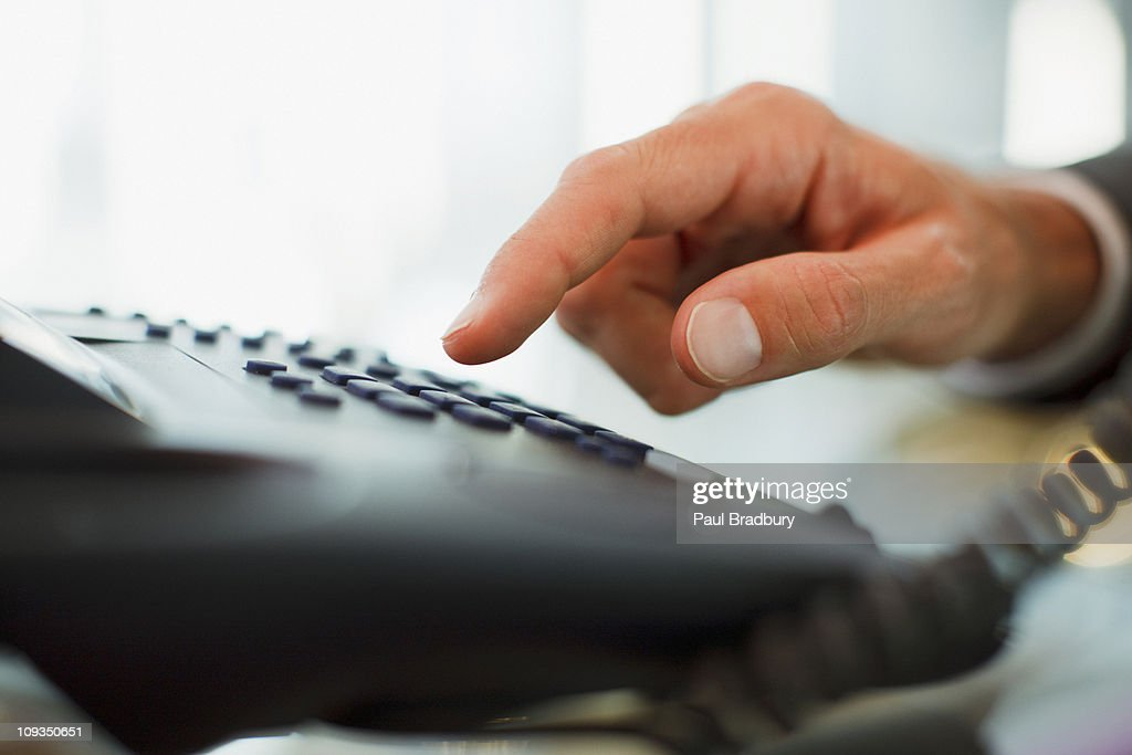 Businessman dialing telephone in office : Stock Photo