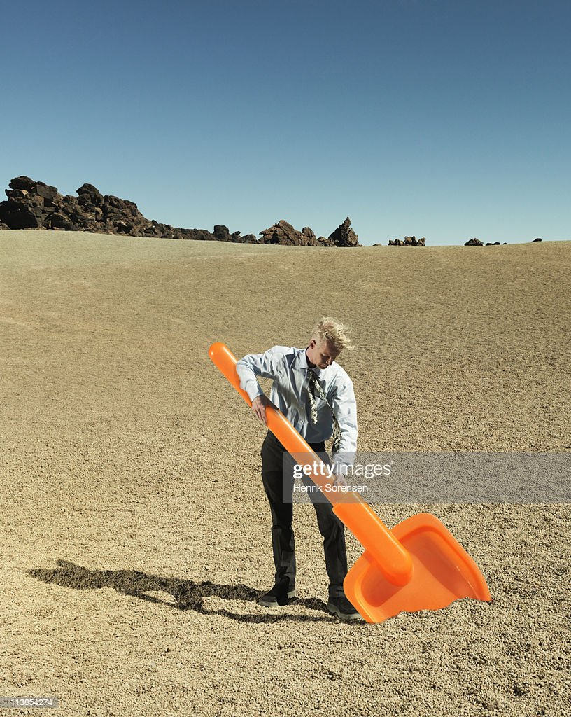 Businessman digging with oversized plastic spade : Stock Photo