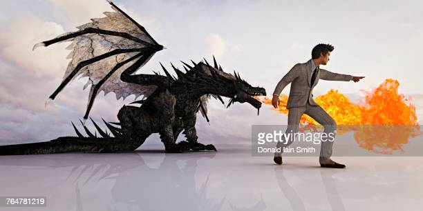businessman directing fire breathing dragon - dragon stock photos and pictures