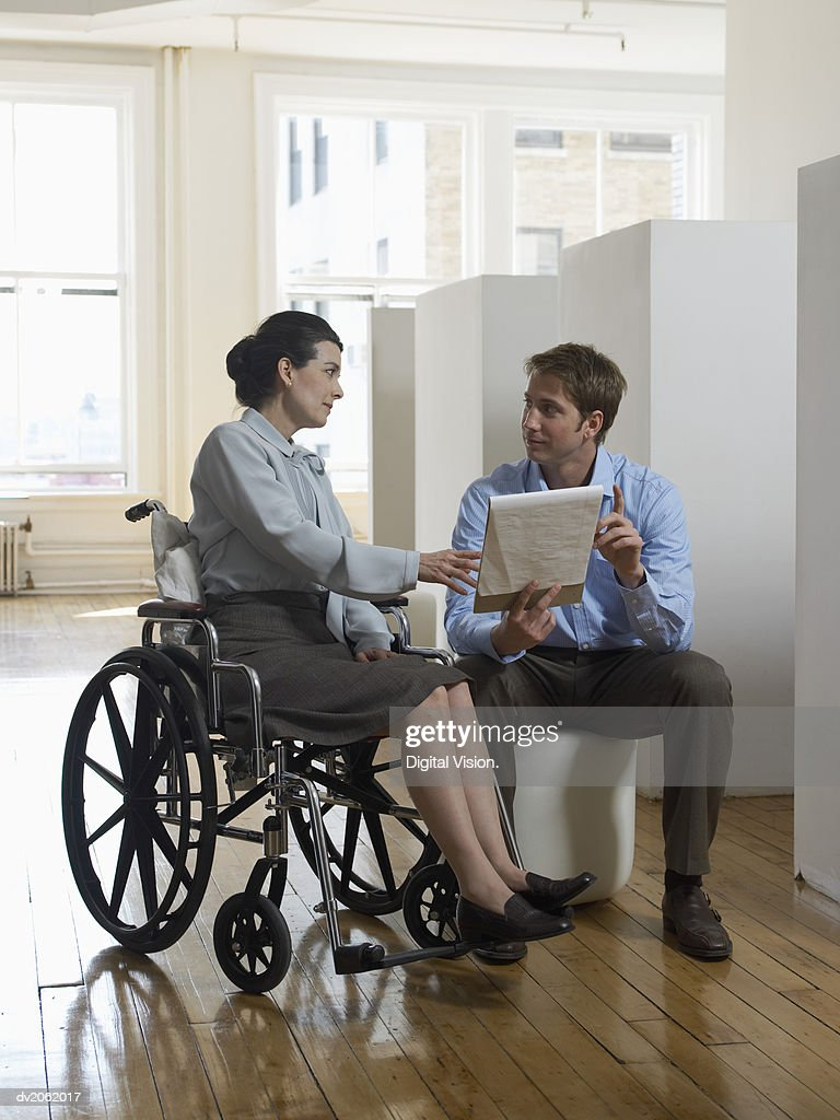 Businessman Discussing a Document With a Businesswoman Sitting in a Wheelchair : Stock Photo