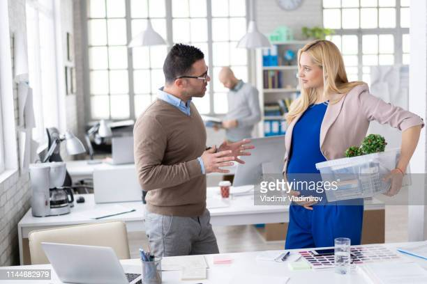 businessman discussing ideas with pregnant colleague at workplace - leaving stock pictures, royalty-free photos & images