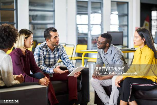 businessman discussing over tablet pc with team - five people stock pictures, royalty-free photos & images