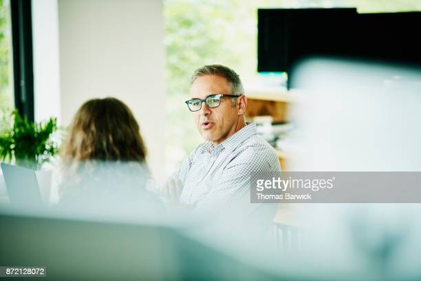 Businessman discussing project with client at office conference table