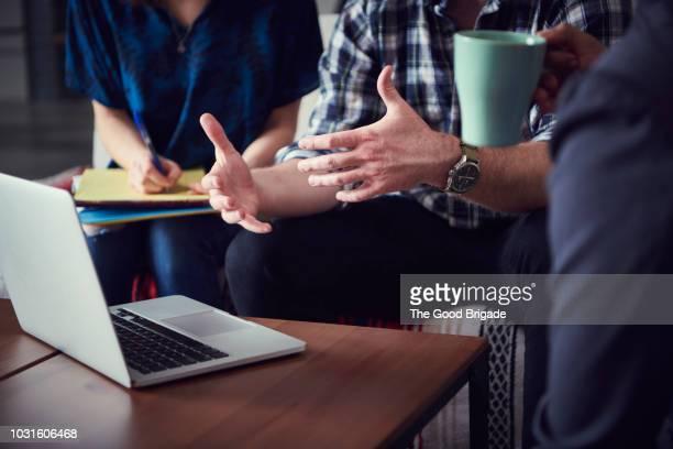 businessman discussing project with coworkers - gestikulieren stock-fotos und bilder