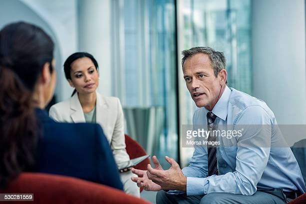 businessman discussing strategy with colleagues - three people stock pictures, royalty-free photos & images