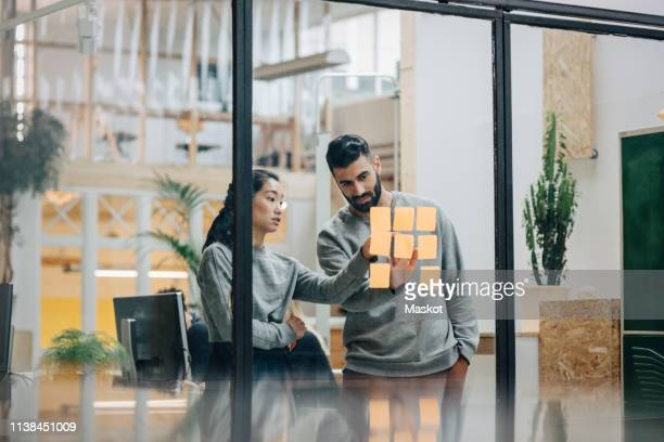 businessman discussing with businesswoman sticking adhesive notes on glass wall in office - oficio creativo fotografías e imágenes de stock