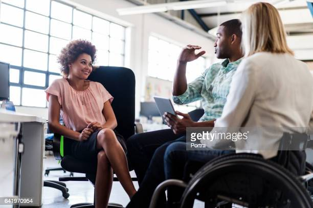 businessman discussing with colleagues in office - wheelchair stock pictures, royalty-free photos & images