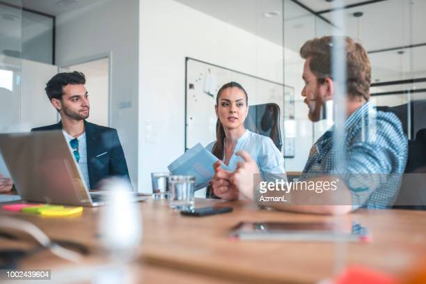 Businessman discussing with coworkers in office