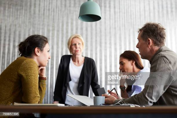 Businessman discussing with female colleagues in board room at creative office
