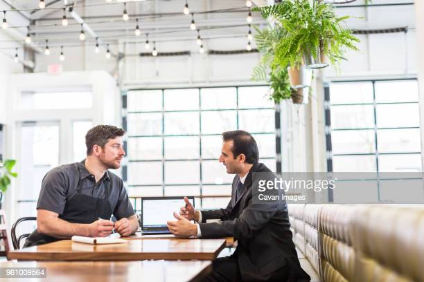 Businessman discussing with male chef in restaurant