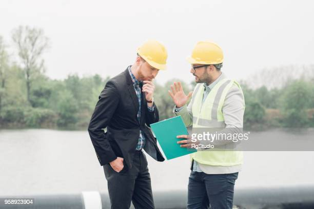 Businessman discussing work with construction worker