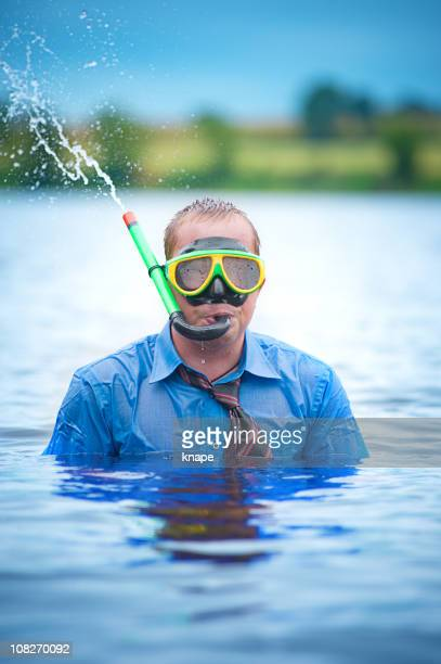 Businessman diving into water with snorkel