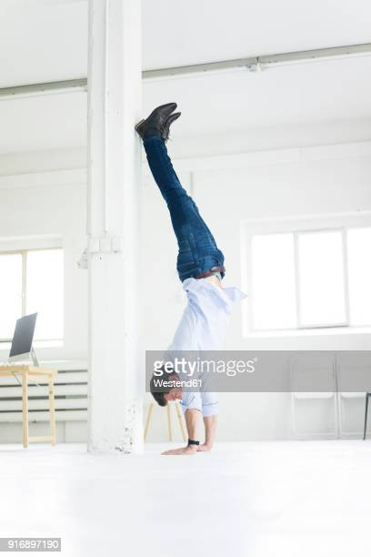 Businessman doing a handstand in office