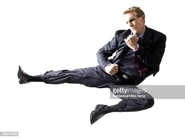 businessman doing a karate kick - 背広 ストックフォトと画像