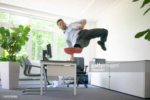 businessman doing a one-handed handstand on desk in office - 離れ技 ストックフォトと画像