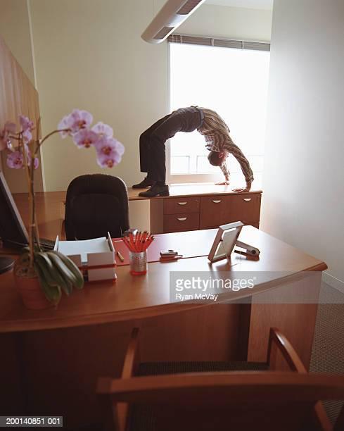 Businessman doing backbend on office desk