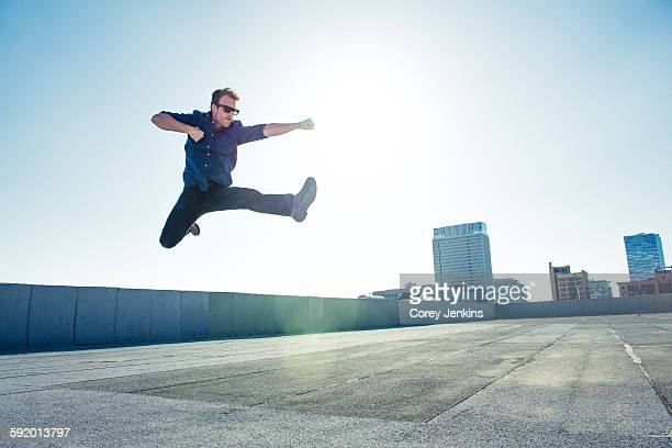 Businessman doing flying kick on roof terrace, Los Angeles, California, USA