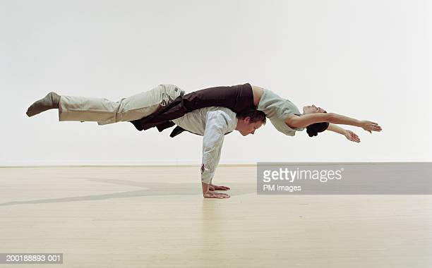 businessman doing handstand, balancing woman on back, side view - acrobatic activity stock pictures, royalty-free photos & images