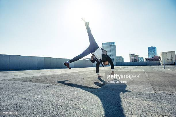 businessman doing handstand on roof terrace, los angeles, california, usa - op z'n kop stockfoto's en -beelden