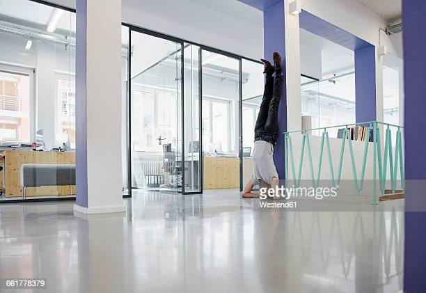 Businessman doing headstand against wall in office