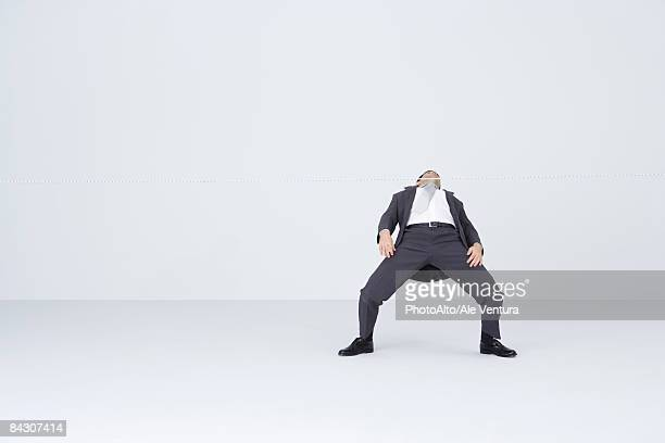 businessman doing limbo, bending backwards to go under rope - benen gespreid stockfoto's en -beelden