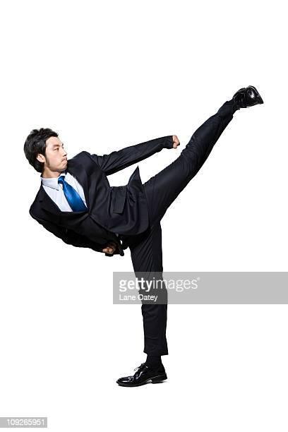businessman doing martial arts kick - 背広 ストックフォトと画像