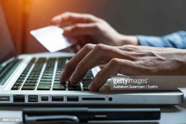 Businessman Doing Online Shopping Through Credit Card On Laptop At Desk