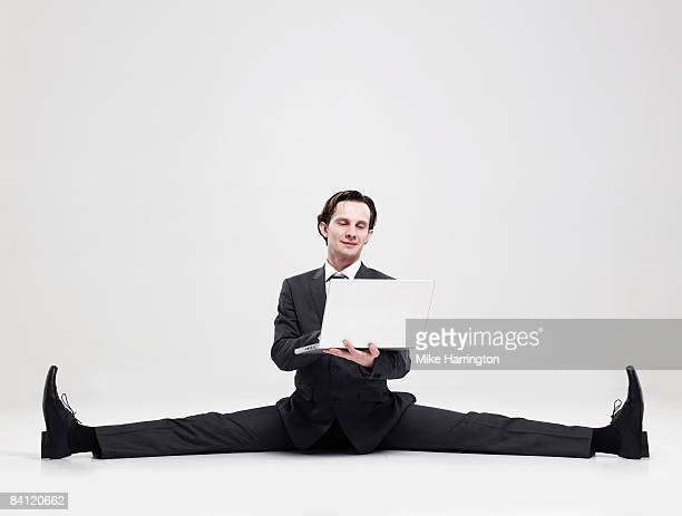 businessman doing the splits holding laptop  - benen gespreid stockfoto's en -beelden